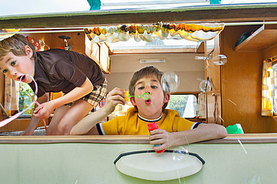 Two boys blowing bubbles out of caravan - p924m664953f by Mieke Dalle