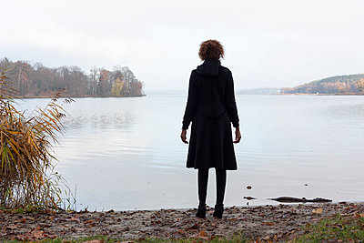 Young woman looking onto the lake - p975m2228555 by Hayden Verry