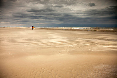 Germany, Lower Saxony, Eastern Friesland, Spiekeroog, couple having a walk at the low tide - p300m1028779f by Peter Schickert