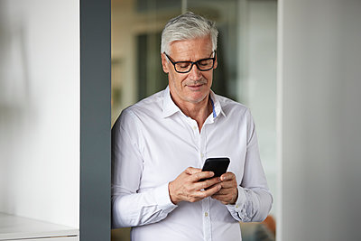 Businessman using mobile phone while standing in office - p300m2282567 by Rainer Berg