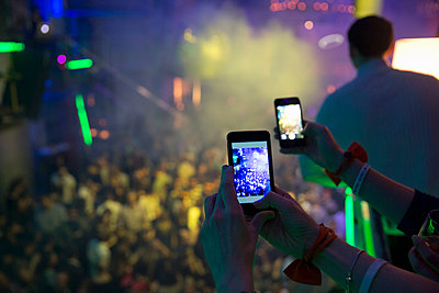Women taking photograph in nightclub with cellular phone - p429m911564f by Philipp Nemenz