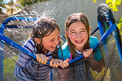 Water splashing on Caucasian girls leaning on netting - p555m1504022 by Marc Romanelli