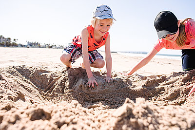Brother and sister playing with sand on beach - p924m2271140 by Viara Mileva