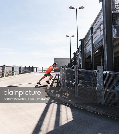 Man jogging in the city, taking a break, stretching - p300m1587366 von Uwe Umstätter