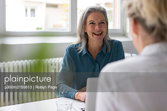 Happy mature businesswoman talking to young businesswoman at desk in office - p300m2155613 by Robijn Page