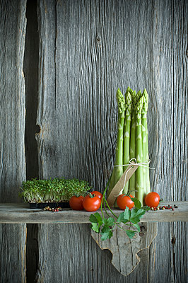 Bundle of green asparagus, tomato, cress, parsley and mixed pepper on wood - p300m2023843 von Achim Sass