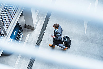 Top view of businessman walking with baggage and takeaway coffee at a car park - p300m2102660 von Daniel Ingold