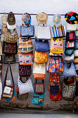 Street market stall with rows of brightly coloured handbags and hats, Khatmandu, Nepal. - p855m664591 by Mike Kirk