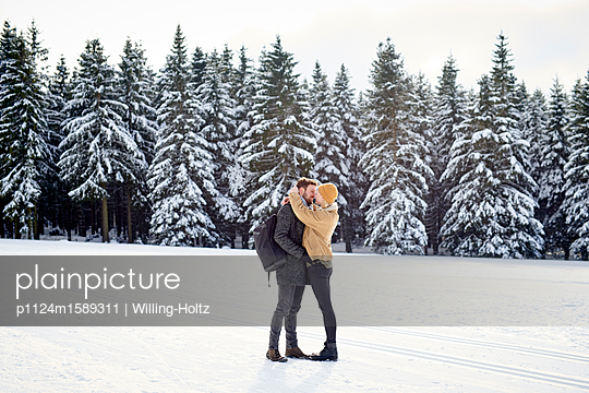 Junges Paar küsst sich in einer Schneelandschaft - p1124m1589311 von Willing-Holtz