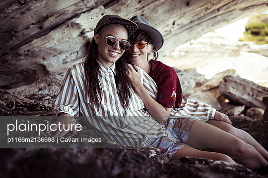 Same sex lesbian couple sit in rocky cliffs on beach holiday in sun - p1166m2136698 by Cavan Images