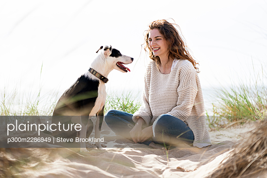 Young woman with red hair sitting in the sand at beach smiling at her dog, Portugal - p300m2286949 von Steve Brookland