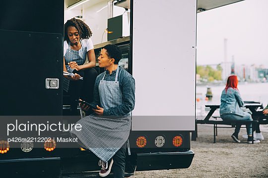 Female owner and assistant discussing in food truck - p426m2212202 by Maskot