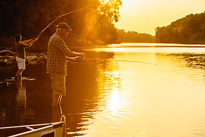 Friends fishing while standing in lake during sunset - p1166m1524914 by Cavan Images