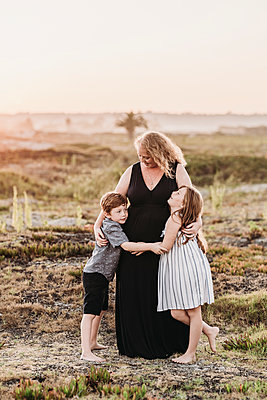 Portrait of redhead mother hugging children at sunset at beach - p1166m2136557 by Cavan Images