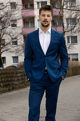 Young man in suit, hands in pockets - p226m2263547 by Sven Görlich