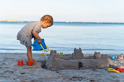 Cute toddler girl building a sand castle on the beach - p300m2143491 by Daniel Ingold