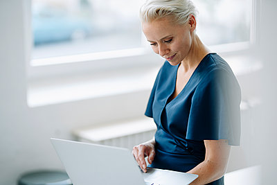 Businesswoman using laptop while sitting in loft office - p300m2214026 by Kniel Synnatzschke