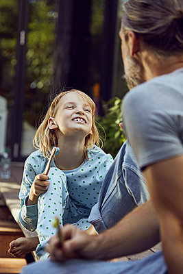 Girl showing teeth to father while brushing with him in yard - p300m2214042 by Maya Claussen