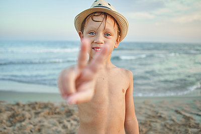 Smiling boy showing peace gesture while standing at beach - p300m2221351 by Veam