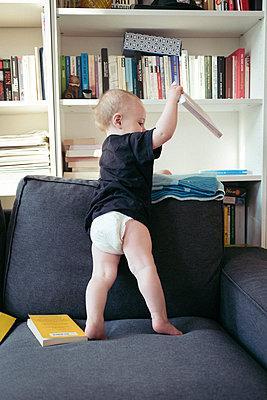 Baby räumt Bücherregal aus - p795m2184265 von JanJasperKlein