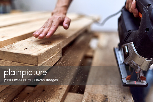 Hands of a young woman cutting wooden pallets with a jigsaw - p1166m2208071 by Cavan Images