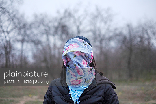 Young woman with a blue scarf with flower motif over her face - p1527m2116783 by Slaveng