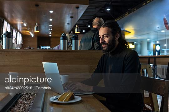UK, London, Man using laptop at airport cafe - p924m2292519 by Tamboly