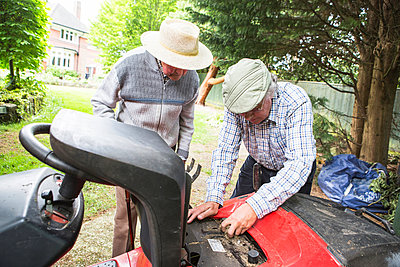 Senior Father and Son fixing together lawn mower - p1026m1164172 by Patrick Frost