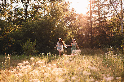 Happy lesbian couple holding hands while running in forest in summer - p1166m2212464 by Cavan Images