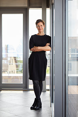 Portrait of smiling woman standing in office - p300m2012969 by Rainer Berg