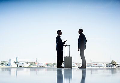 Two businessmen on airfield - p586m1208570 by Kniel Synnatzschke