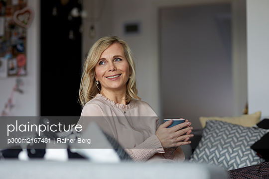 Smiling blond woman relaxing at home sitting on couch - p300m2167481 by Rainer Berg