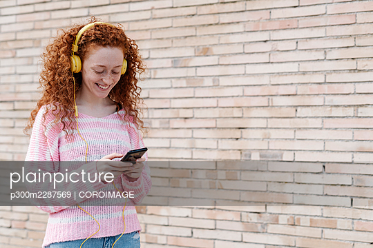 Smiling young woman using smart phone while listening music through headphones by wall - p300m2287569 by COROIMAGE