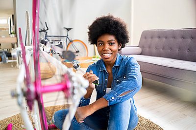 Happy young woman repairing bicycle at home - p300m2274794 by Giorgio Fochesato