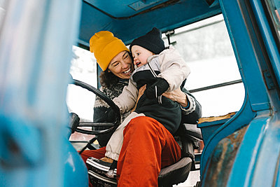 Cheerful mother with daughter sitting in tractor during winter - p426m2284685 by Maskot