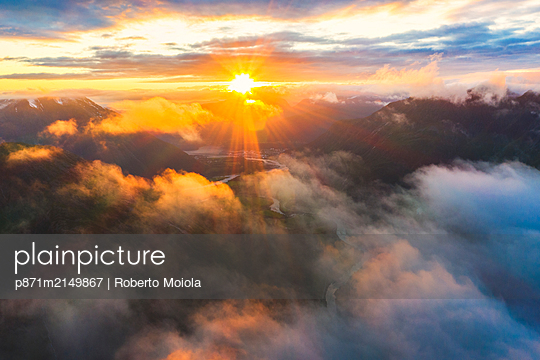 Aerial view of sun rays at sunset lighting up the clouds over Romsdalen valley, Andalsnes, More og Romsdal county, Norway, Scandinavia - p871m2149867 by Roberto Moiola