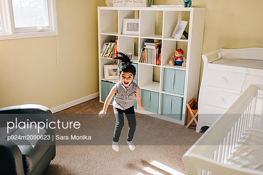 Girl jumping mid air in nursery, portrait - p924m2090623 by Sara Monika