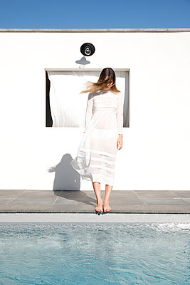Young woman in summer dress stands at the poolside - p1105m2200698 by Virginie Plauchut