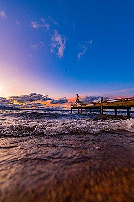 Woman on boardwalk at sunrise, New Zealand - p1455m2204871 by Ingmar Wein