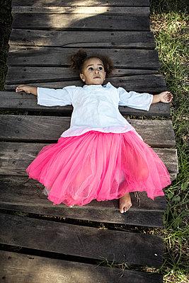 Little girl in pink tulle skirt lying on back - p1640m2246847 by Holly & John