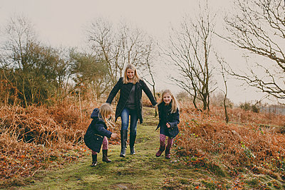 Mother and daughters running on a meadow together - p300m1449608 by Nicole Matthews
