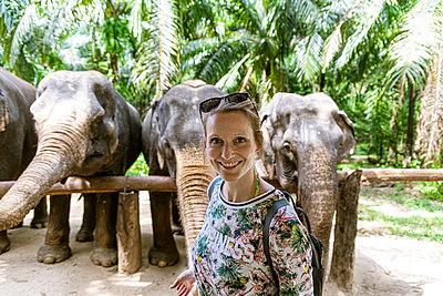 Portrait of smiling woman with elephants in sanctuary, Krabi, Thailand - p300m2166279 by Christophe Papke