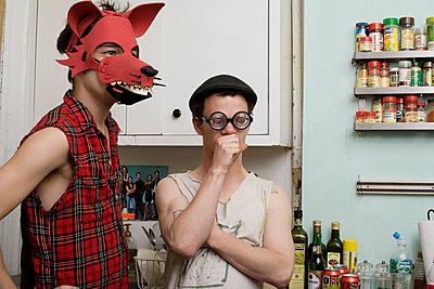 Two young men standing in a kitchen wearing silly disguises - p3019025f by Antenna photography