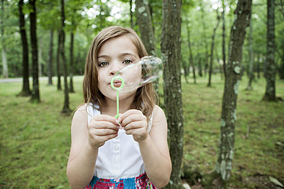 Girl blowing bubbles in forest - p924m711198f by Bill Miles