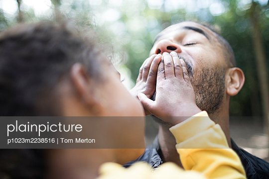 Playful daughter covering mouth of father - p1023m2238516 by Tom Merton