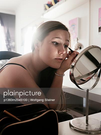 Junge Frau trägt Make-Up auf - p1383m2045100 von Wolfgang Steiner