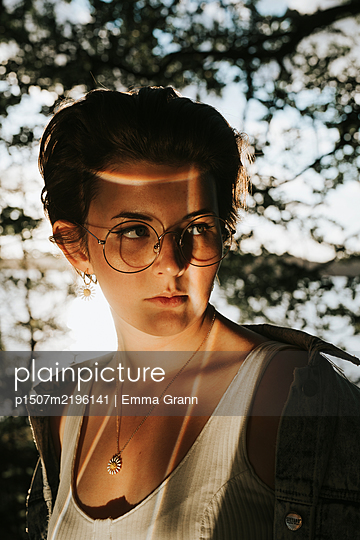 Girl with glasses in reflecting light - p1507m2196141 by Emma Grann