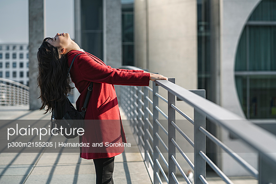 Modern businesswoman getting relaxed standing on a bridge, Berlin, Germany - p300m2155205 by Hernandez and Sorokina