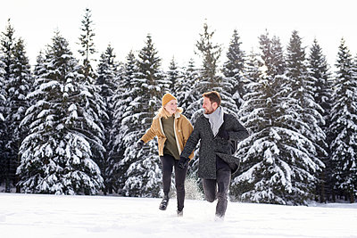 Young couple romping around in snowy landscape - p1124m1589334 by Willing-Holtz