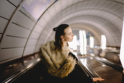 Young woman standing on escalator at subway station - p1166m2138109 by Cavan Images